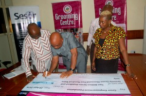 CEO Grooming Centre, Dr Godwin Nwabunka, signing the chque